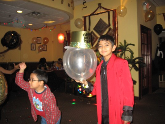 Young boy balances the hat on balloon